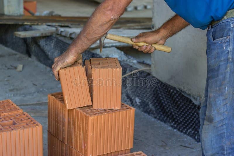 Byggmästarearbetare som klipper ett lerakvarter med tegelstenhammaren arkivbilder