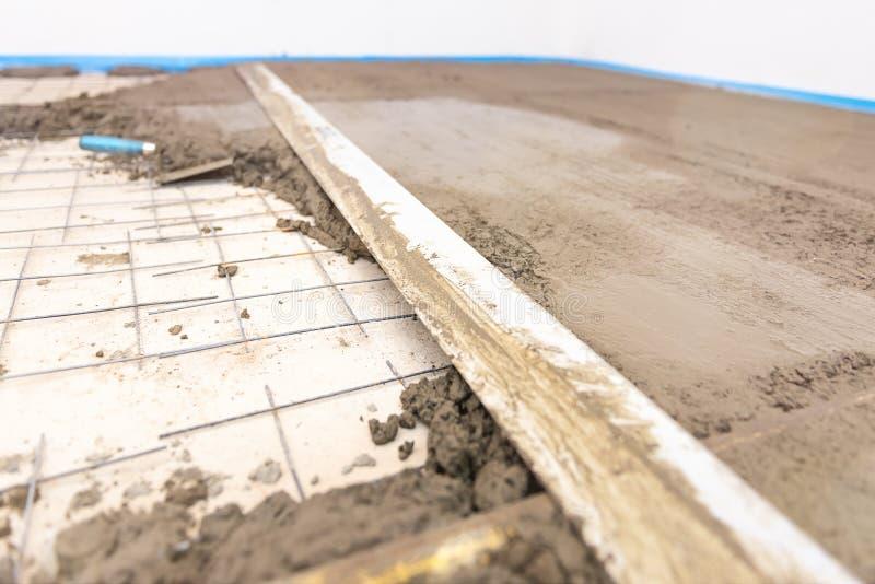 Byggmästarearbetare som rappar betong på golvet av huskonstruktion arkivbilder