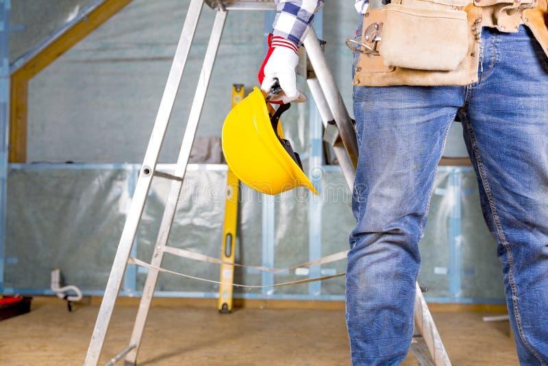 Byggmästarefaktotum med den gula säkerhetshjälmen och hjälpmedelbälte på atti arkivbilder