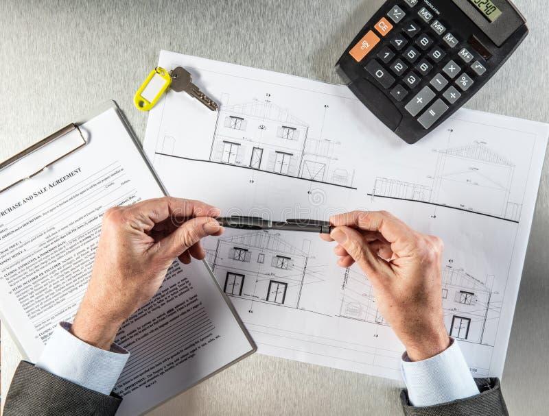 Byggmästarehänder med tangent och hus formulerar att tänka om förhandling royaltyfria foton