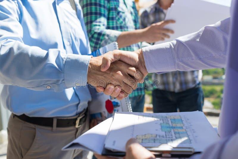 ByggmästarehandskakningCloseup, två byggande affärsmän som gör avtal efter diskussion av ritningen till det nya projektet med royaltyfri foto