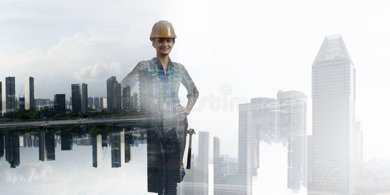 Byggmästarekvinna mot cityscape arkivbild