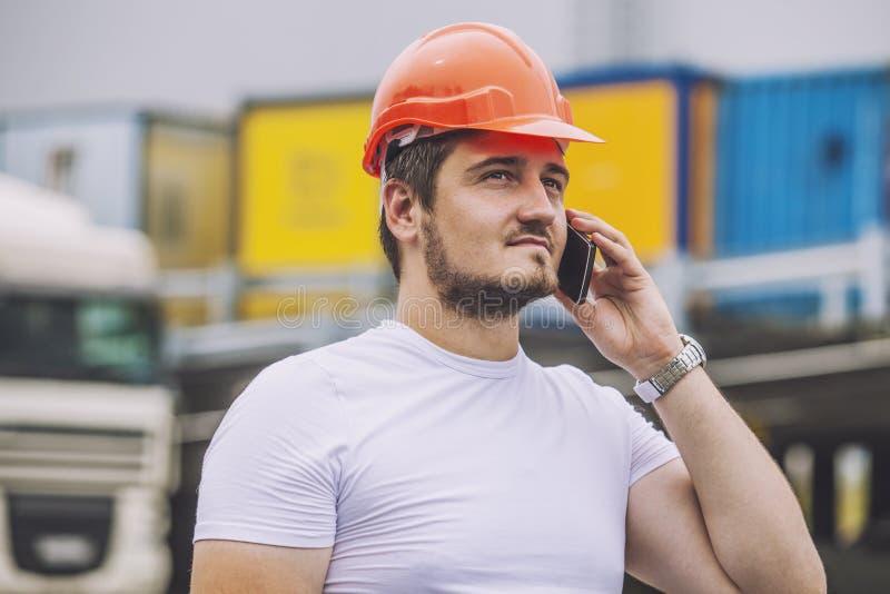Byggmästareman som arbetar med en mobiltelefon i en skyddande hjälm royaltyfri bild
