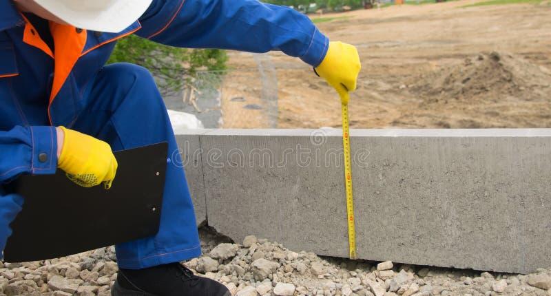 Byggmästaren, i en vit hjälm och en blå likformig, kontroller framsteget av lägga av kantsten, kullen av spillror och tagande arkivbilder