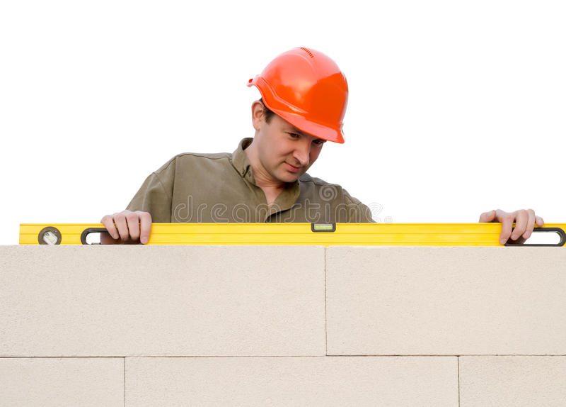 Byggmästaren kontrollerar en nivå royaltyfri fotografi