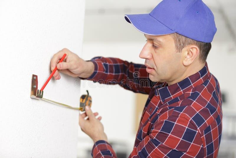 Byggmästaren markerar på väggen med linjalen och blyertspennan fotografering för bildbyråer