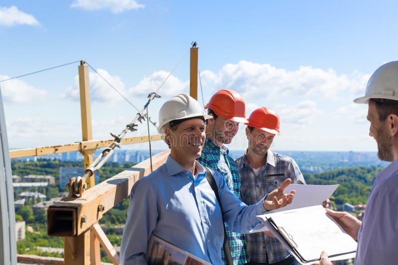 ByggmästareTeam Meeting With On Construction plats som diskuterar projektplan med arkitekten Contractor arkivbilder