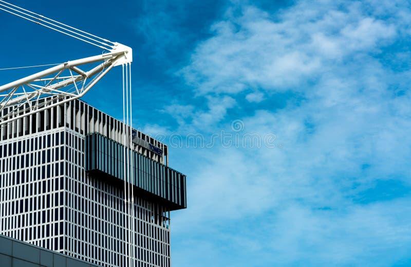 Byggnad av kontoret nära moln för konstruktionsplats och för blå himmel och vit Affärstornbyggnad av företaget fotografering för bildbyråer