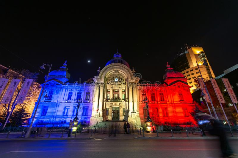 Byggnad för CEC för festival för Bucharest fläckljus historisk med hologrammet av den rumänska nationsflaggan royaltyfri bild