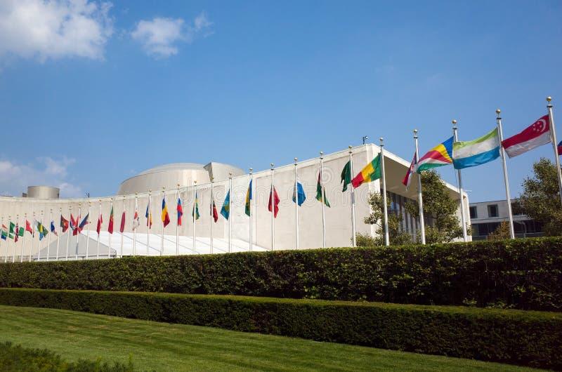 Byggnad för FN-Förenta Nationernageneralförsamling med världsflaggor flyger royaltyfri fotografi