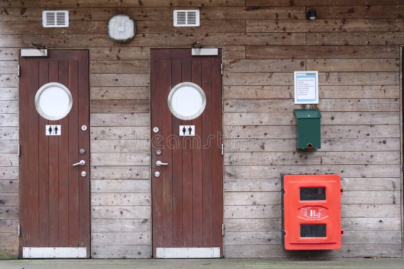 Byggnad för skogen för offentliga toaletter för campingplatsen spanar manlig kvinnlig wood för fotgängarecampare handböcker royaltyfri fotografi