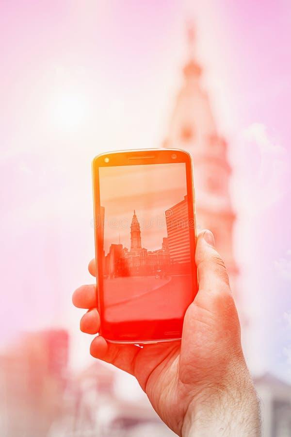 Byggnad f?r stadshus f?r gr?nsm?rke f?r Philadelphia ` s historisk Mannen gör foto på en smartphone Fragment detaljer Philadelphi royaltyfri bild