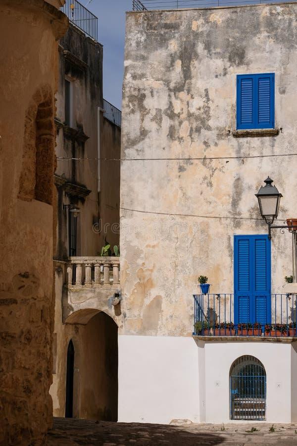Byggnad med blåa slutare på en gata i kuststaden av Otranto på den Salento halvön, Puglia, södra Italien fotografering för bildbyråer
