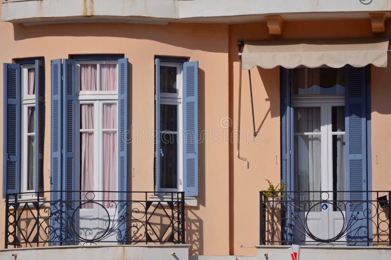 Byggnad med vita fönster och blåa vindskupefönster arkivfoton