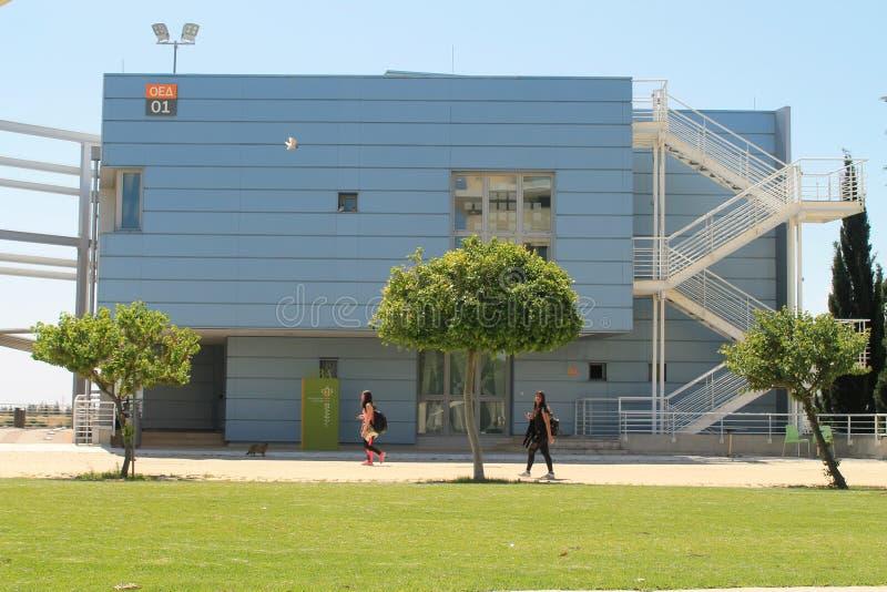 Byggnad, träd och studenter i universitetsområde royaltyfri bild