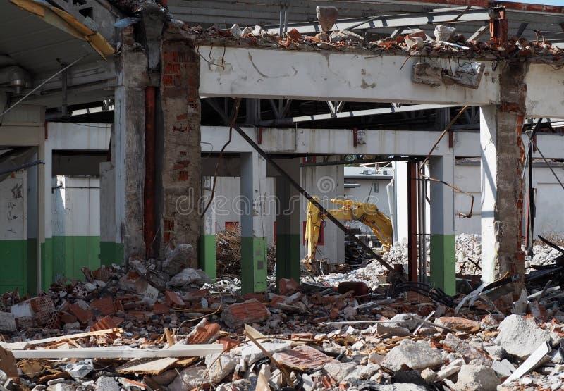 Byggnad under rivning för en stads- sanering På bakgrund en hydraulisk bang av en grävskopa royaltyfria bilder