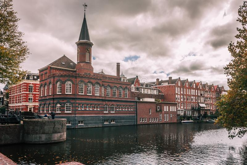 Byggnad vid den Amsterdam kanalen på en lynnig dag arkivbilder