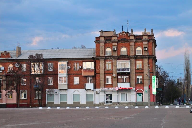 Byggnaden på den centrala fyrkanten i Severodonetsk, Luhansk region, Ukraina Aftoncityscapesolnedgång arkivfoto