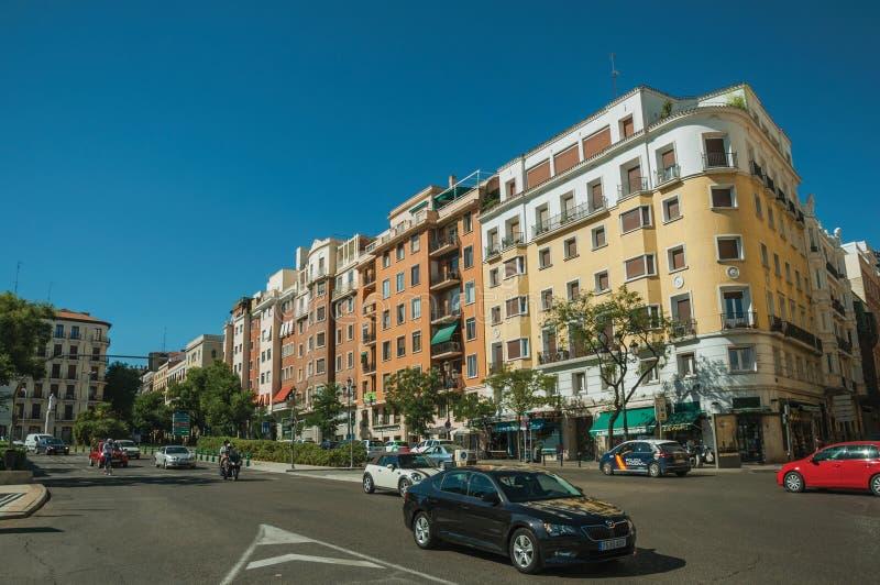 Byggnader med den färgrika fasaden på trägatan med bilar i Madrid fotografering för bildbyråer