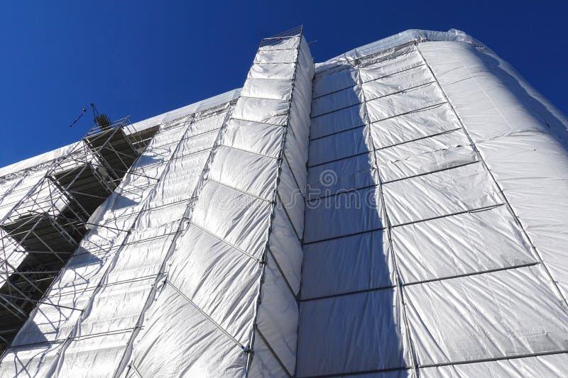 Byggnadsåterställande, byggnaden som täckas med en grå presenning arkivfoton