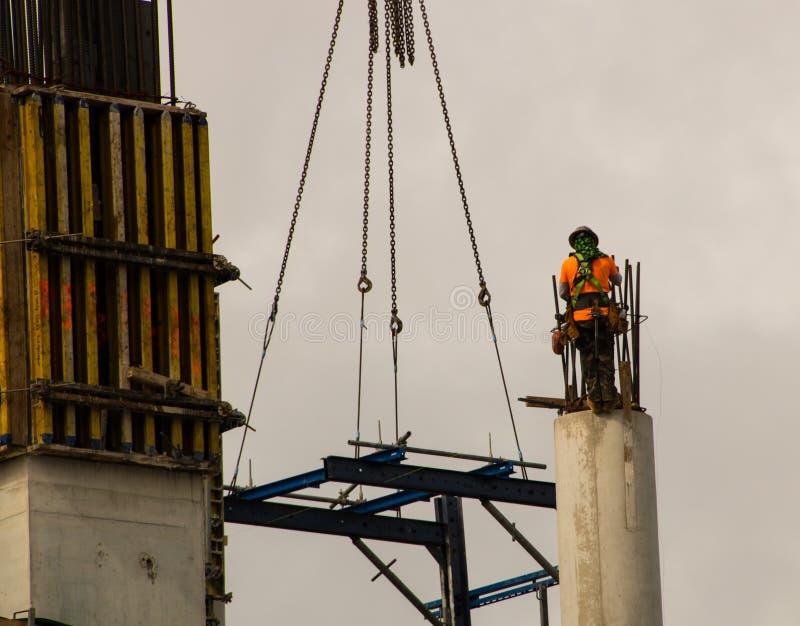 Byggnadsarbetare överst av den konkreta pelaren arkivfoto
