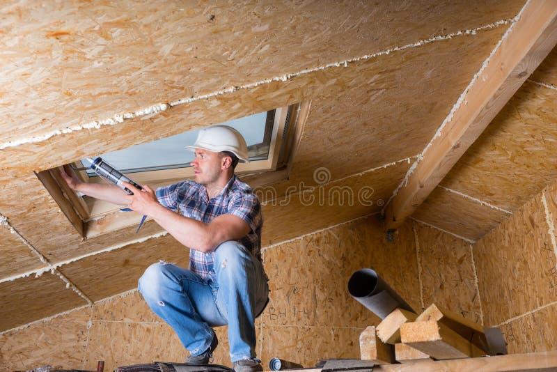 Byggnadsarbetare Applying Caulking till himmelljus arkivbilder