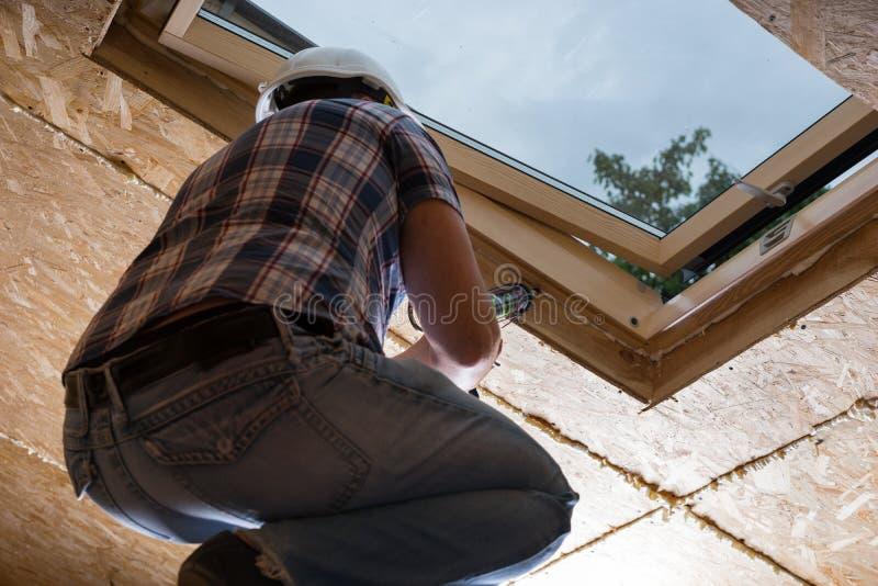 Byggnadsarbetare Applying Caulking till himmelljus arkivfoton