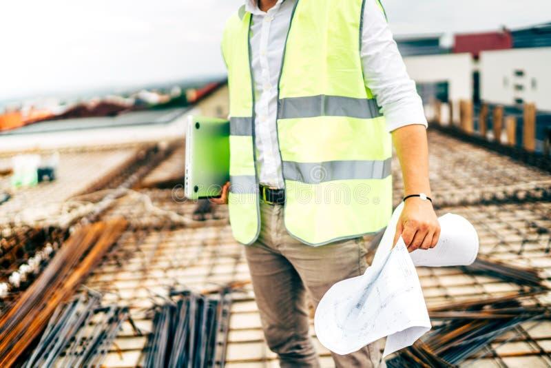 byggnadsarbetare, bärande säkerhetsväst för tekniker och bärbar dator på konstruktionsplats arkivfoto