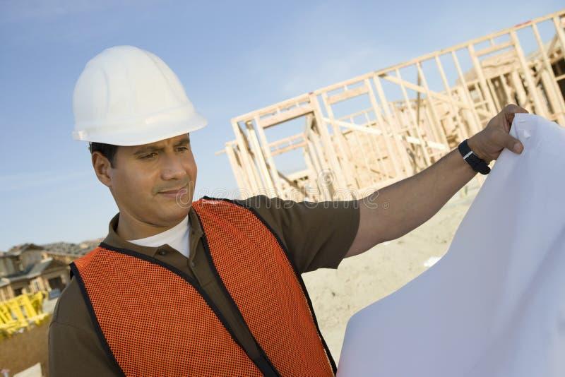 Byggnadsarbetare With Blueprints royaltyfri bild