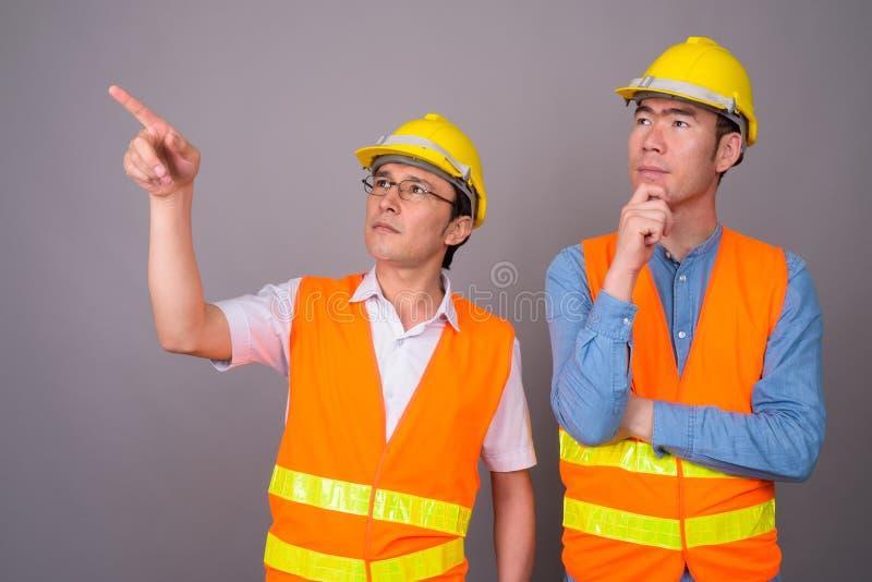 Byggnadsarbetare för två ung asiatisk män tillsammans mot gråa lodisar arkivfoto