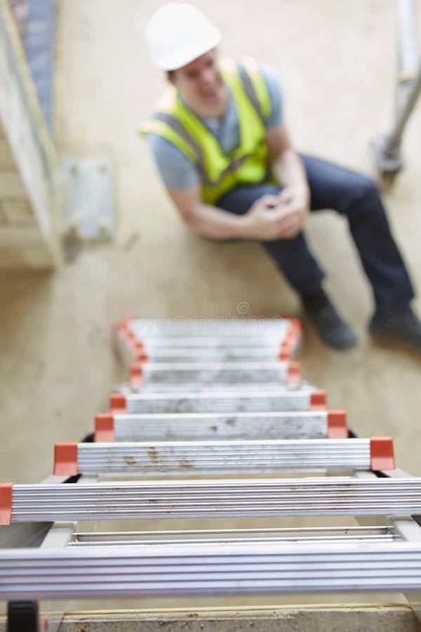 Byggnadsarbetare Falling Off Ladder och såraben arkivfoto