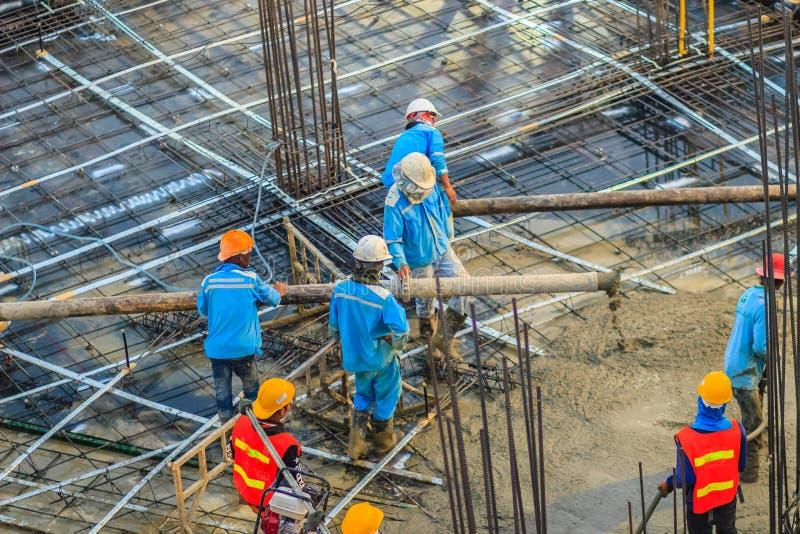 Byggnadsarbetare häller betong i stolpe-spänning floori fotografering för bildbyråer