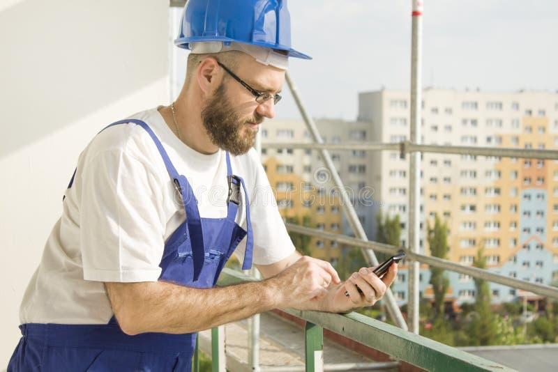 Byggnadsarbetare i arbetskläder och en hjälm som rymmer en mobiltelefon i hans hand och ringer ett nummer Arbete på hög höjd Sc royaltyfri fotografi