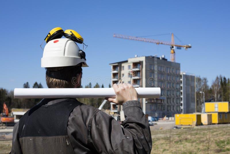 Byggnadsarbetare i smutsiga overaller och en vit hjälm i Finland royaltyfri foto