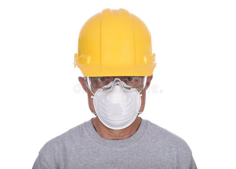 Byggnadsarbetare i utslagsplatsskjortan som bär en hård hatt, skyddsglasögon och dammmaskeringen som isoleras över vit royaltyfri bild