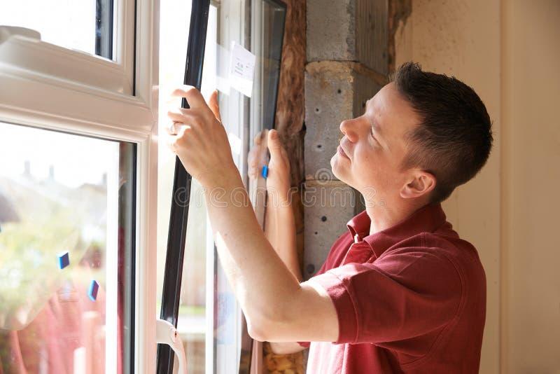 Byggnadsarbetare Installing New Windows i hus arkivbilder