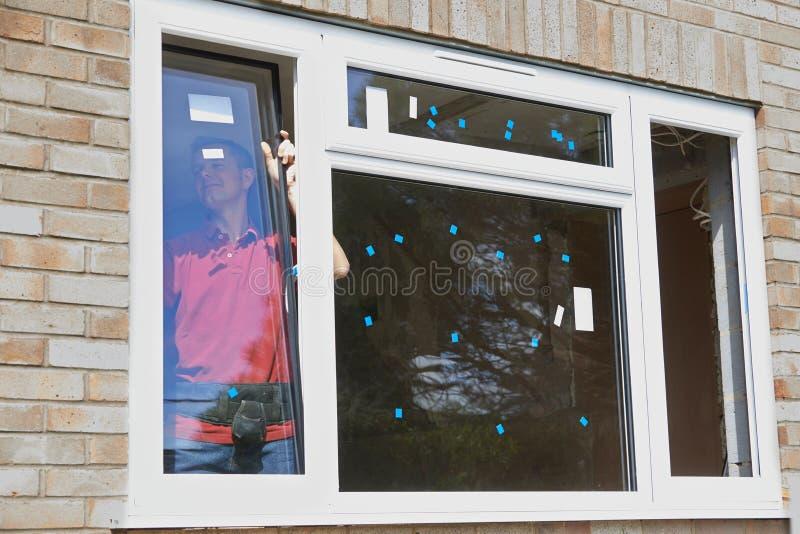 Byggnadsarbetare Installing New Windows i hus royaltyfria foton