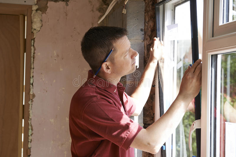 Byggnadsarbetare Installing New Windows i hus royaltyfri foto