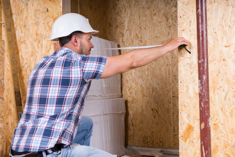 Byggnadsarbetare Measuring Width av dörrramen arkivbilder