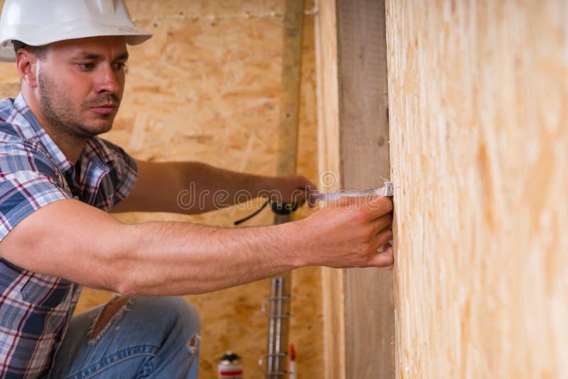 Byggnadsarbetare Measuring Width av dörrramen royaltyfria foton