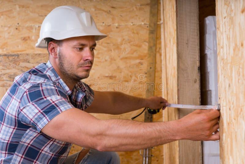 Byggnadsarbetare Measuring Width av dörrramen arkivfoto