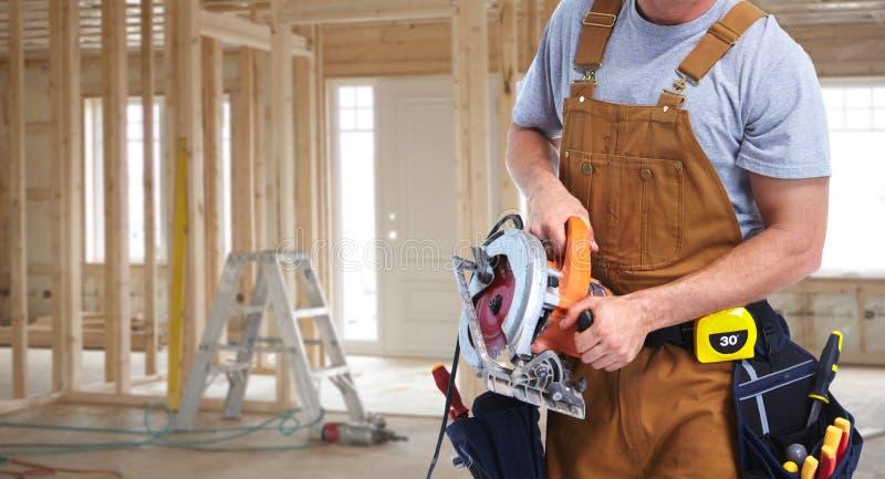 Byggnadsarbetare med den elektriska sågen arkivbild