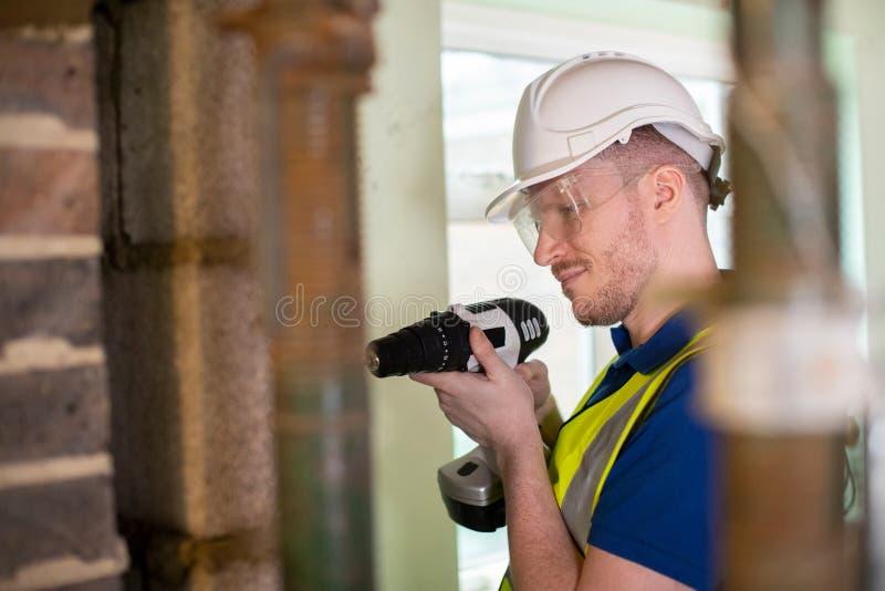 Byggnadsarbetare med den sladdlösa drillborrborrandeväggen i renoverat hus royaltyfri bild