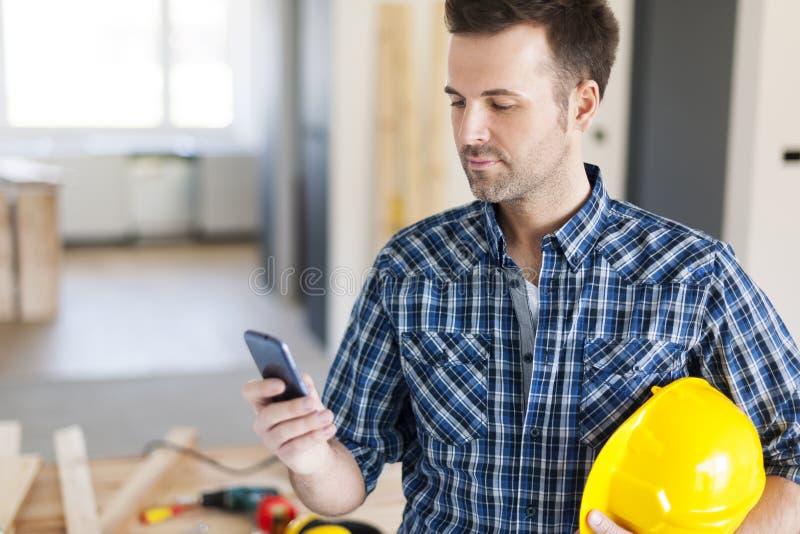 Byggnadsarbetare med den smarta telefonen royaltyfri bild