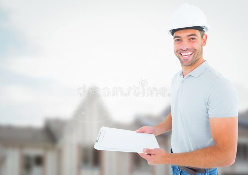 Byggnadsarbetare med diagrammet som är främst av konstruktionsplats arkivfoto