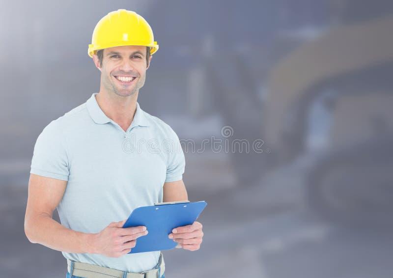 Byggnadsarbetare med diagrammet som är främst av konstruktionsplats arkivbild