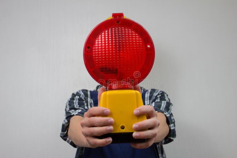 Byggnadsarbetare med en röd konstruktionsplats-lampa royaltyfri bild