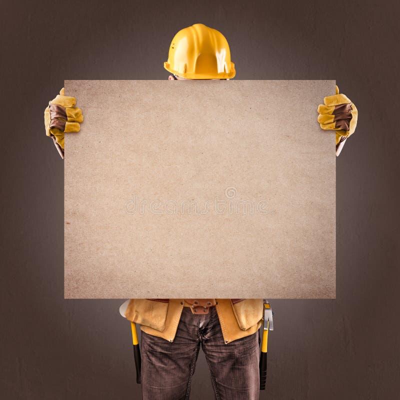 Byggnadsarbetare med informationsaffischer på en brun backgrou arkivbild