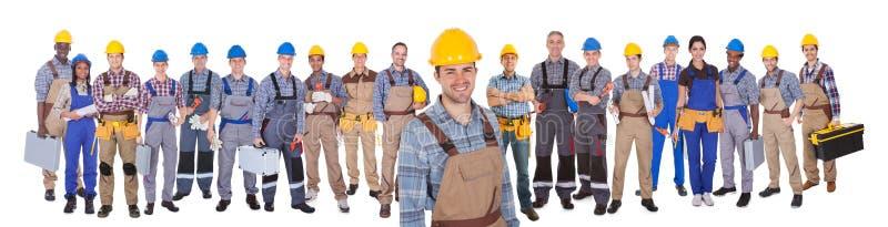Byggnadsarbetare med kollegor över vit bakgrund royaltyfria foton