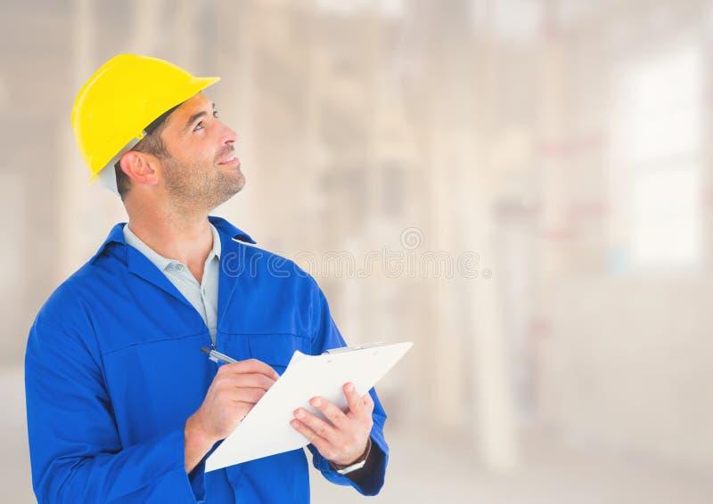 Byggnadsarbetare med penndiagrammet framme av konstruktionsplatsen arkivbild